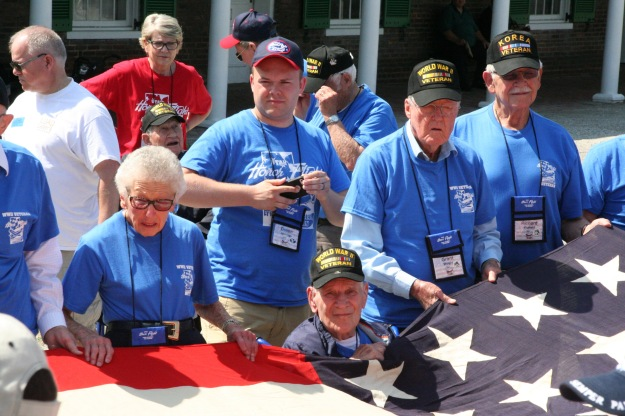 Dean Ravert (in red) participating in a flag raising ceremony at Fort McHenry, along with veterans from a Utah Honor Flight group.